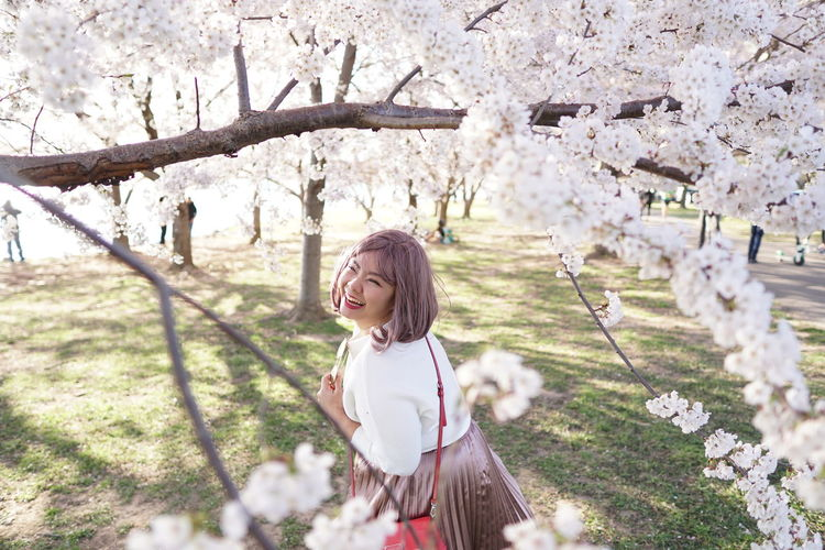 Woman standing by cherry blossom