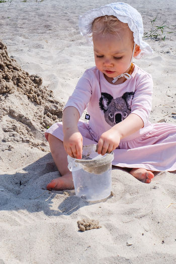 Child Childhood Beach Land Real People Innocence Leisure Activity Day Nature Outdoors Sand Dune Playing In Sand Sand Ocean Playing Father One Person Front View Girls Full Length Cute Casual Clothing Container Women Baby Girl