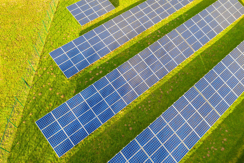 High angle view of solar panels on grassy field