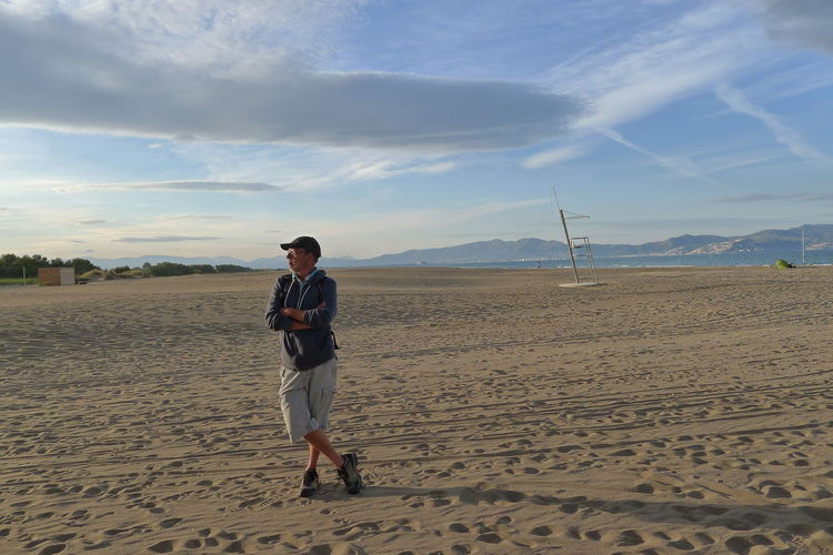 Full length of man standing on sandy beach against sky