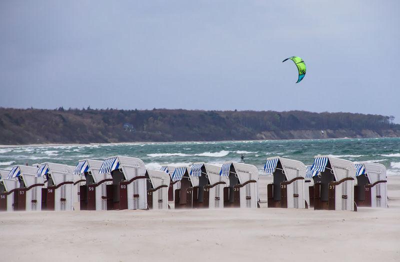 Hooded beach chairs at beach against clear sky