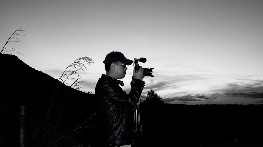 Side view of man photographing against sky during sunset