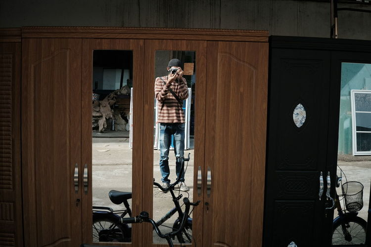 Man photographing with camera reflecting on mirror of cupboard