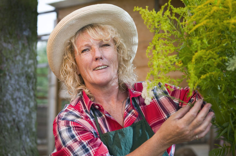 Portrait Of Woman Wearing Hat While Touching Plant