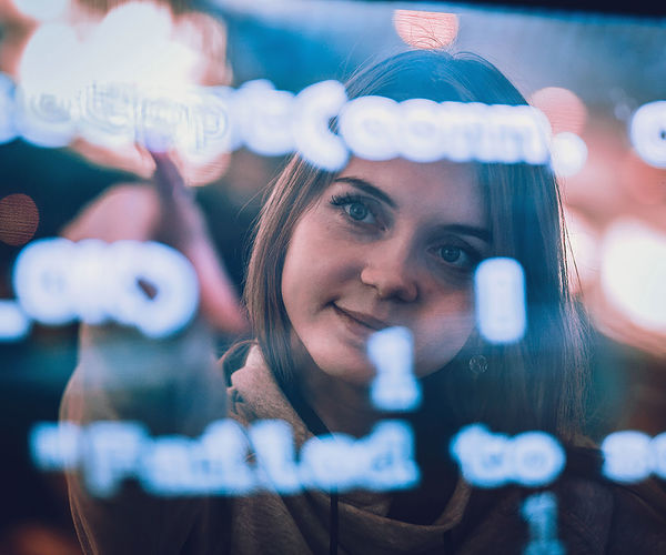 Futuristic. young woman behind the transparent screen with codes.