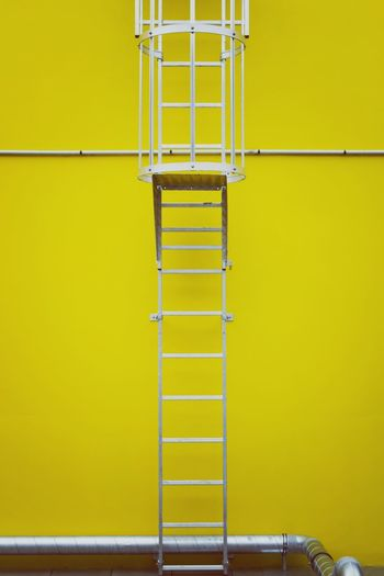 Metallic ladder against yellow wall