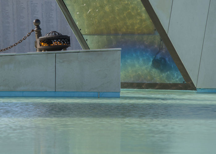 Eternal Flame By Water Against Glass Wall