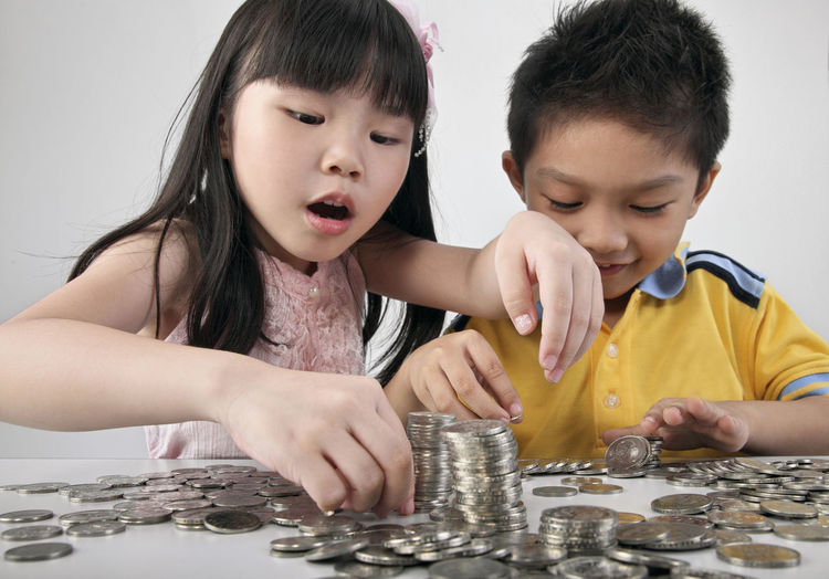 Children counting coins on table against white background