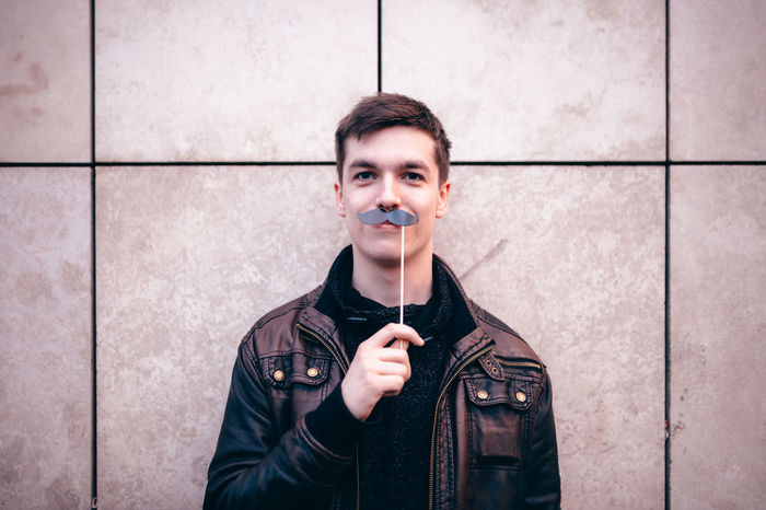Teenagers posing with party props Adult Adults Only Beard Caucasian Day Front View Leisure Activity Looking At Camera Movember Mustache One Man Only One Person Only Men Outdoors Party People Portrait Props Real People Smiling Standing Teenager Wall Young Adult