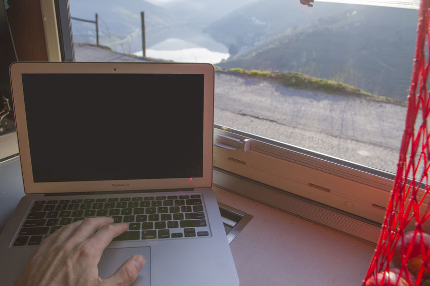 Working on laptop with beautiful view through window of vehicle/motorhome Close-up Computer Computer Keyboard Day Human Body Part Human Hand Indoors  Laptop Mountain One Person People Technology Using Laptop Wireless Technology