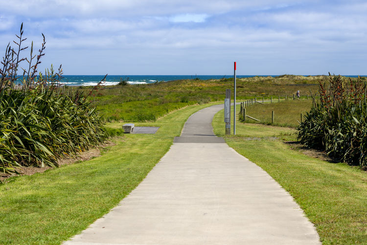 Footpath amidst grass and sea against sky