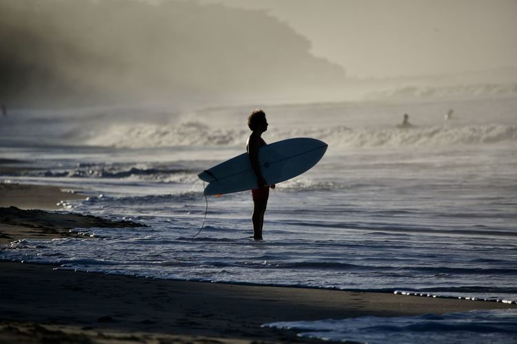 Sea Water Land Beach Wave Surfing Sport One Person Aquatic Sport Leisure Activity Motion Surfboard Real People Lifestyles Sky Beauty In Nature Sports Equipment Nature Horizon Over Water Skill  Outdoors