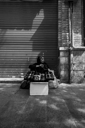 Woman selling sunglasses while sitting on footpath against closed shutter
