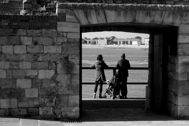 Through The Doorway Black & White Family Architecture Blackandwhite Built Structure Day Doorway Leisure Activity Outdoors People Real People Rear View Sea Standing Togetherness Water