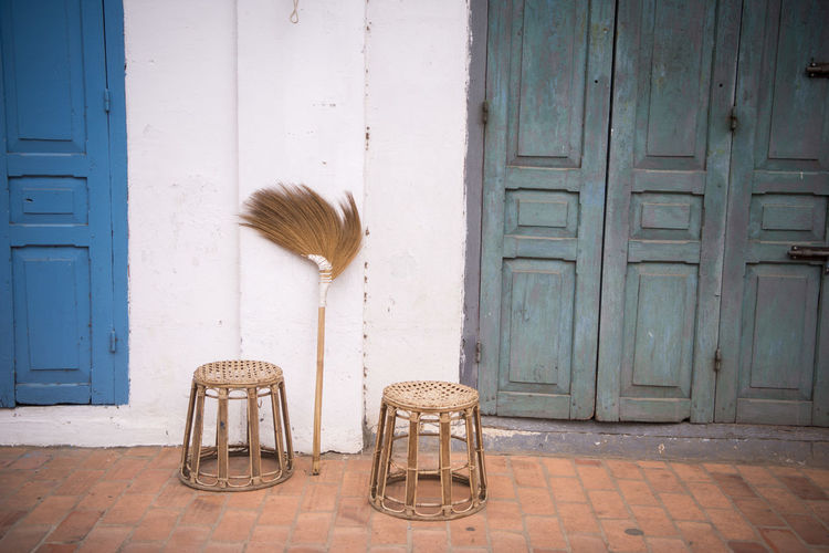 Stools And Broom By Closed Doors Outside House
