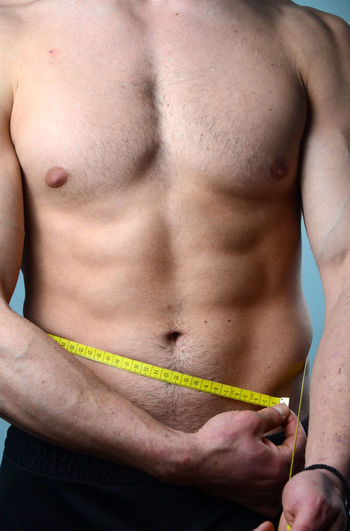 Midsection Of Shirtless Man With Tape Measure