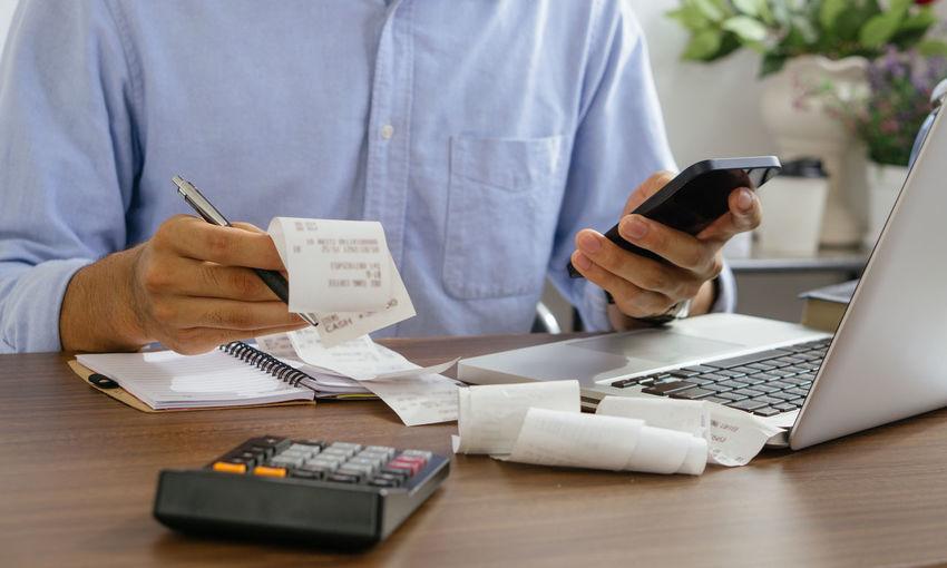 The man holding paper bills using calculator app. calculation financial.