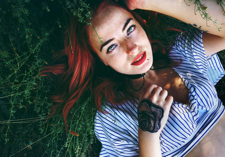 Portrait of young woman lying on field