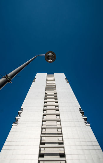 Low angle view of building and street light against clear blue sky