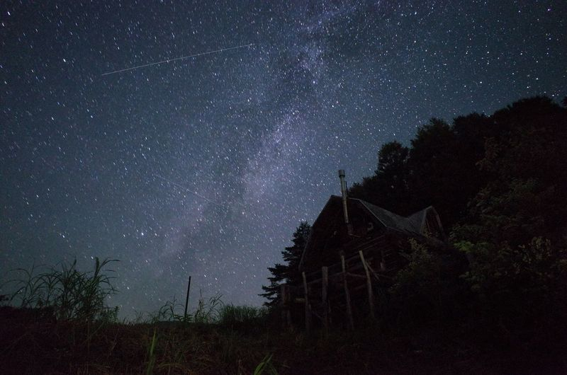 Low angle view of log cabin with stars in sky at night