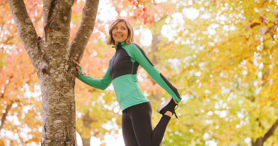 Autumn Day Exercising Forest Happiness Healthy Lifestyle Leaf Leisure Activity Lifestyles Low Angle View Mid Adult Mid Adult Women Motion Nature One Person Outdoors Real People Smiling Sports Clothing Standing Tree Tree Trunk Women Young Adult Young Women
