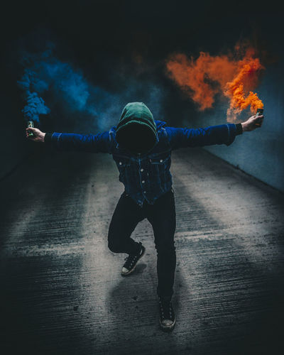 Full length of man holding distress flares against black background