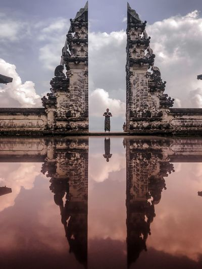 Man standing at entrance of temple with refection against sky