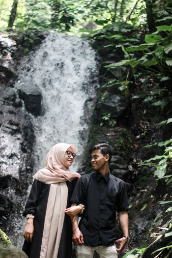Smiling couple standing arm in arm against waterfall