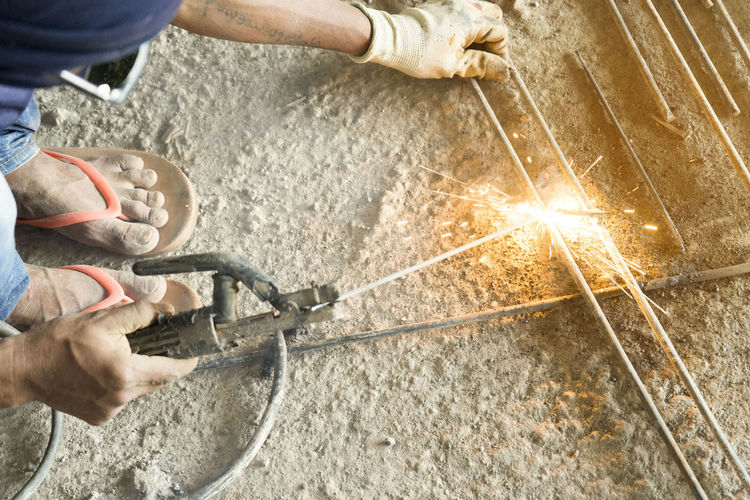 Midsection of man welding metal at construction site