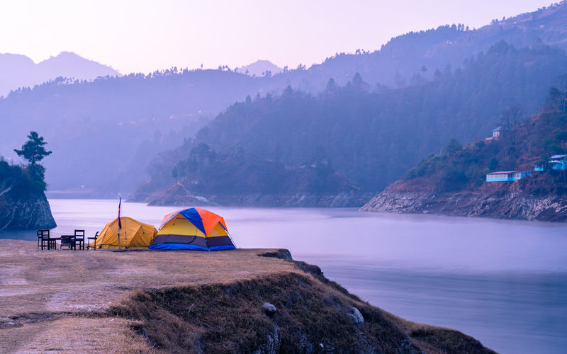 Tent on rock by lake against sky