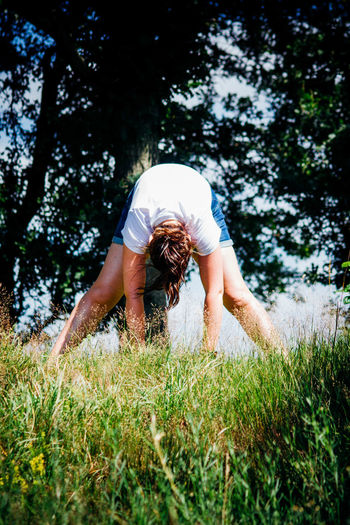 Young Woman Exercising On Grassy Field