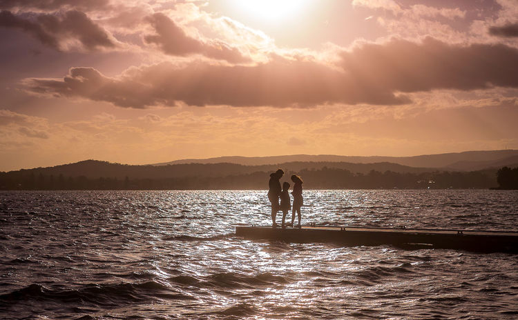Dramatic Sky Family Sillhuette Sunlight Beauty In Nature Cloud - Sky Couple - Relationship Lens Flare Lifestyles Men Mountain Nature Outdoors Positive Emotion Real People Scenics - Nature Sea Silhouette Sky Standing Sun Sunlight Sunset Togetherness Tranquility Two People Water Waterfront