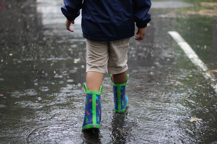 Low Section Of Boy Walking In Puddle