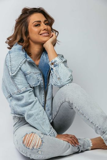 Young woman smiling while sitting against wall