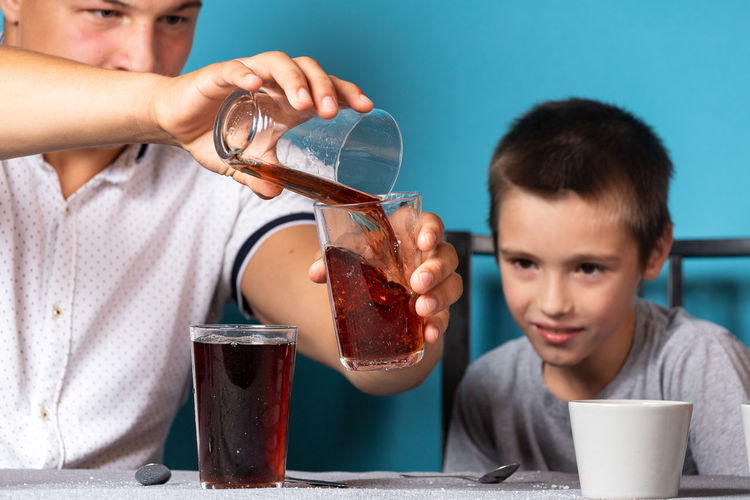 High angle view of boy drinking glass on table