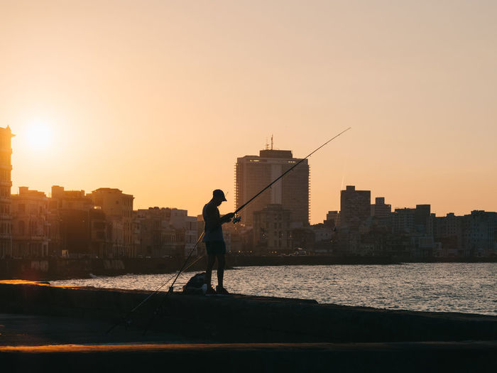 Silhouette man standing by buildings against sky during sunset