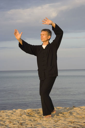 Full length of mature man practicing tai chi on sea shore at beach against cloudy sky