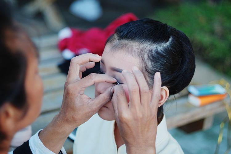Artist applying make-up on young woman