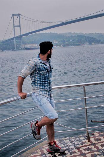 Full length of man standing against bridge over sea