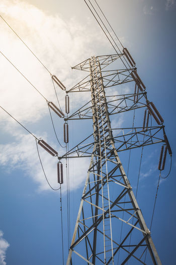 electricity transmission pylon against blue sky Built Structure Cable Cloud - Sky Connection Directly Below Electrical Equipment Electricity  Electricity Pylon Fuel And Power Generation Low Angle View Metal Outdoors Power Line  Power Supply Sky Technology