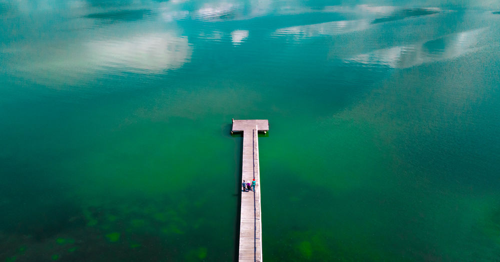Drone aerial view from above of three people walking along a long wooden board jetty surrounded by a blue and green lake. Australia Aerial Copy Space From Above  Holiday Jetty Lake Landscape Looking Down Three People Water Tranquility High Angle View Blue Tranquil Scene Turquoise Colored Sunny Surrounded By Water Unidentifiable People Travel Walking Sunshine Vacation, Board Outdoors