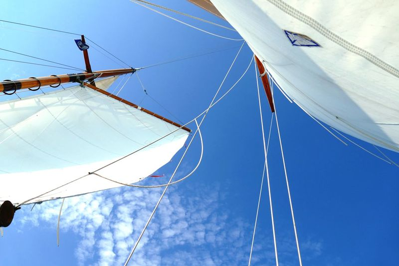 Low angle view of sailboat against blue sky