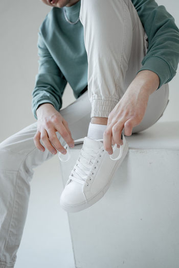 Low section of man wearing shoe