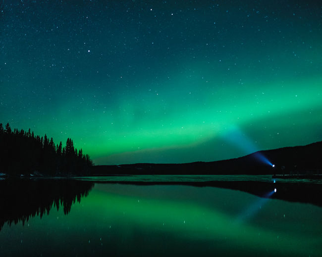 Man standing at clear reflecting lake with head lamp shining into aurora filled night skies