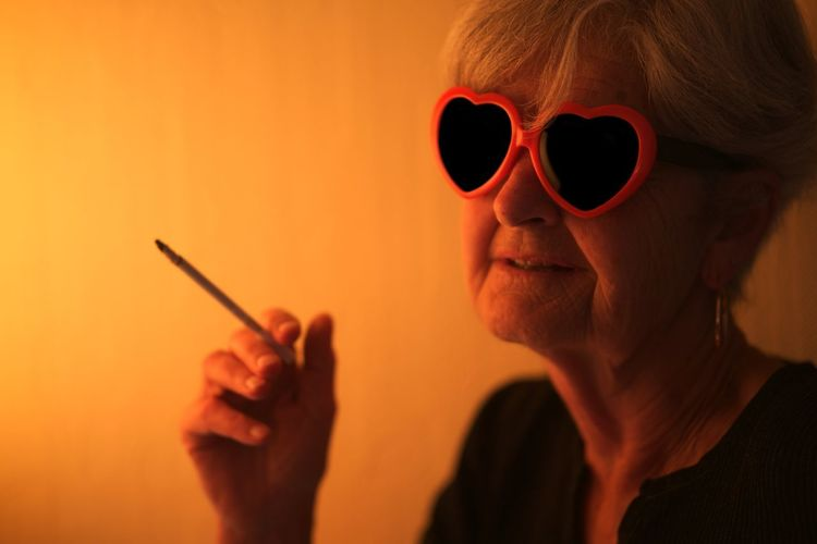 Senior Woman Wearing Heart Shape Sunglasses Smoking Cigarette At Home
