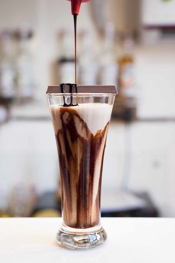 Close-up of chocolate syrup pouring in coffee