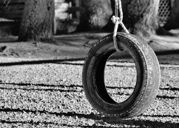Close-up of tire hanging over footpath