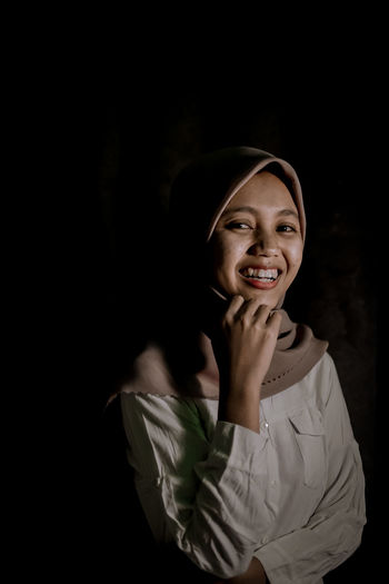 Portrait of a smiling young woman against black background