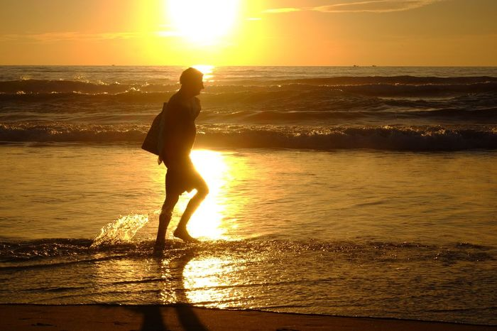 Walking seaside Orange Color Silhouette Sun Sea Beauty In Nature Sunlight Reflection Beach Horizon Over Water Lifestyles Water Holiday Summer Sunshine Tourist Enjoy Lifestyle Vacation Time Day Golden Light Passing Sunset Rimlight Evening