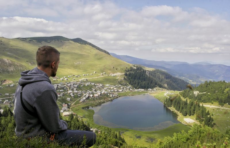 High angle view of man looking at lake while sitting on mountain against cloudy sky